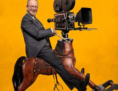 Harry Enfield riding a rocking horse with a old school film camera for a head