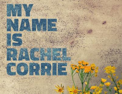 A beige, pock-marked, finely textured wall bares the words 'MY NAME IS RACHEL CORRIE' in a rich sky blue. Wild bright yellow flowers peek up in the right hand bottom corner.