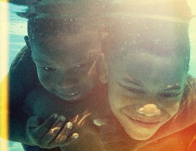 Two young boys under the water smiling, holding each other tightly