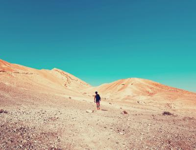 Boy walks through a desert towards two arid hills under a bright blue sky