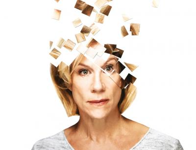 Portrait of Juliette Stevenson in front of a white background with the top of her fragmented into square puzzle pieces