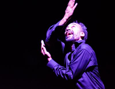 Man in a darkly lit atmosphere, arms stretched, looking upwards