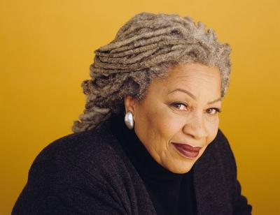 A colour photo of a smiling Toni Morrison against a yellow background