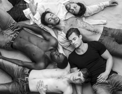 A group of 5 men lay on sand in various states on undress. One has his eyes open whilst the others have theirs closed.