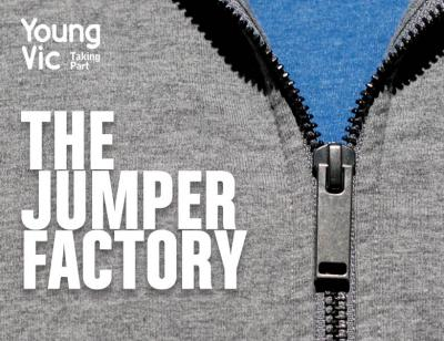 A zoomed in image of a grey hooded sweatshirt, focussing on the zip detail. We can see the blue t-shirt beneath. The words THE JUMPER FACTORY hover in white in front of the image, along with 'Young Vic Taking Part in the top left hand corner