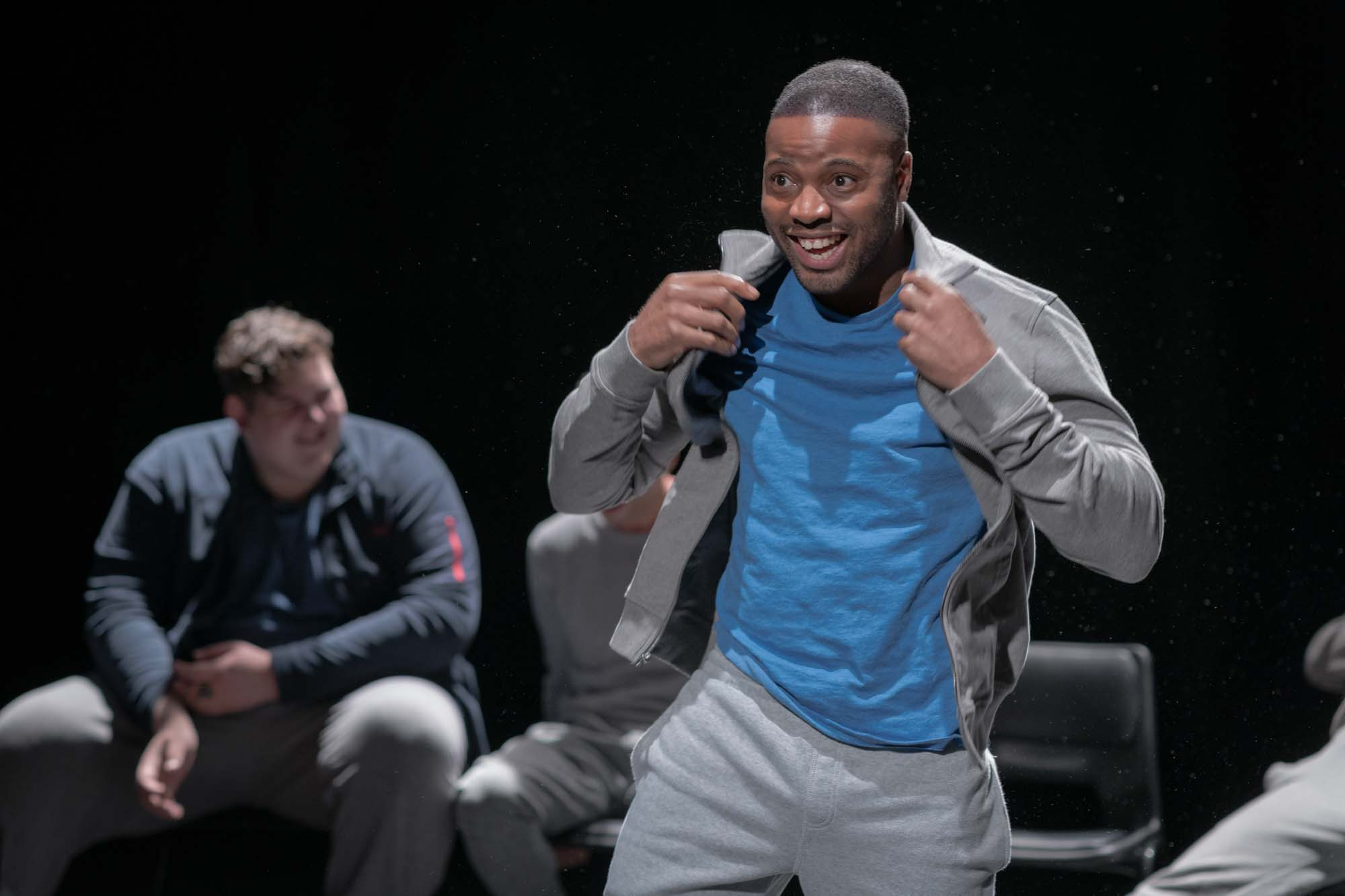 ced165d7f9ae44 ... A grinning male performer adjusts the collar his hoodie
